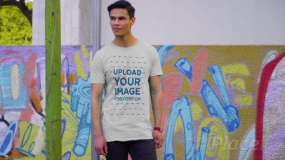 T-Shirt Video of a Young Man Walking by a Wall with Street Art 3113v