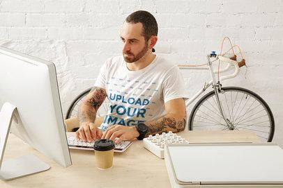 T-Shirt Mockup of a Tattooed Man Working at His Desk M6287-r-el2