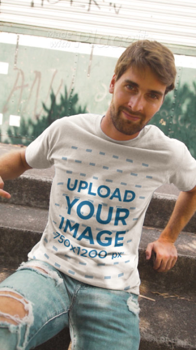 T-Shirt Video of a Man Sitting on a Stair Step Pointing at His Garments 3643v