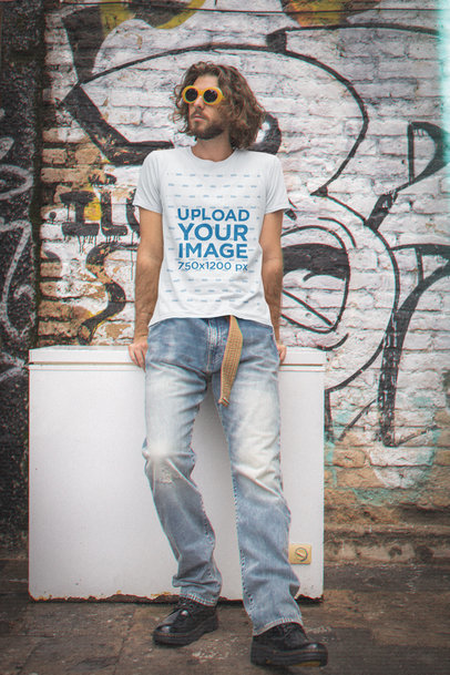 90s-Styled T-Shirt Mockup Featuring a Man Posing Against a Graffitied Wall m12537