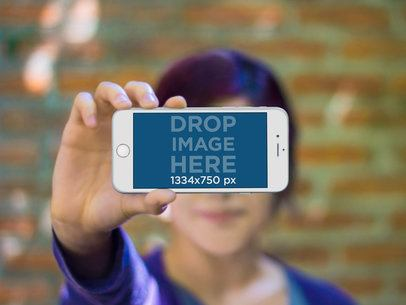 Woman Holing iPhone 6 Frontal Shot Brick Wall