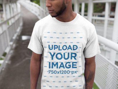 Black Man Walking on a Bridge While Wearing a Round Neck Tee Mockup a16893