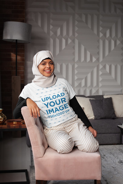 Transparent T-Shirt Mockup of a Woman Wearing a Hijab Casually Sitting on a Couch 28399