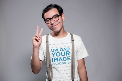 Transparent Smiling Nerd Wearing a T-Shirt Mockup and Suspenders Doing the Peace Sign a19356