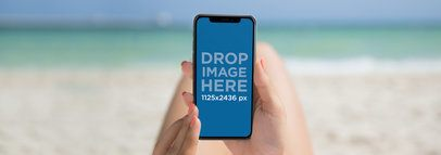 Girl Holding an iPhone X Mockup while at the Beach a17286