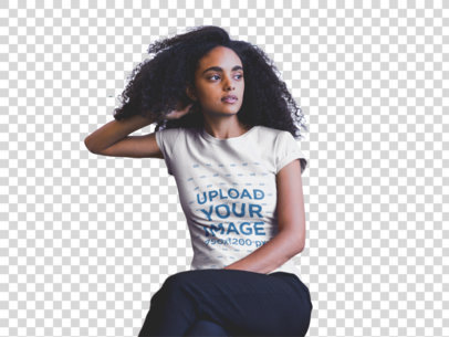 Transparent Mockup of a Young Woman with Curly Hair Wearing a T-shirt and nSitting on a Sofa 20395
