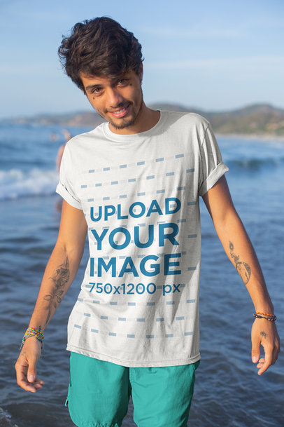 Transparent Mockup of a Tattooed Young Man by the Sea Wearing a T-Shirt 26767