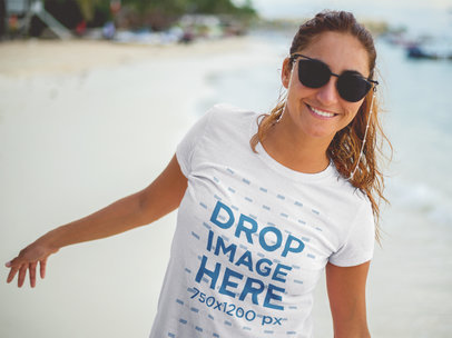 Transparent Smiling Lovely Woman Wearing a T-Shirt Mockup and Sunglasses at the Beach a12725