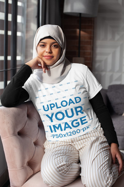 Transparent T-Shirt Mockup of a Woman in a Hijab Sitting on a Couch 28400