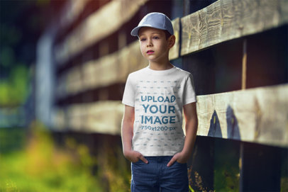 Transparent Mockup of a Boy Wearing a Customizable T-Shirt and Standing by a Wooden Fence 2919-el1