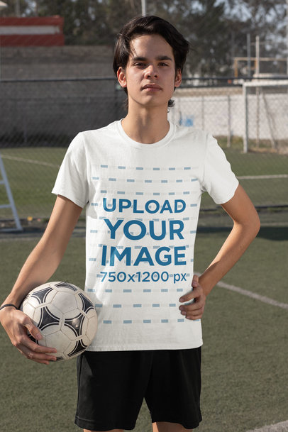 Transparent T-Shirt Mockup Featuring a Serious Teenage Boy Holding a Soccer Ball 33569