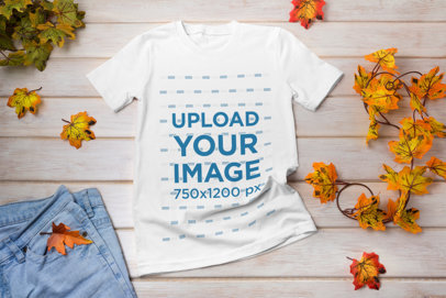 Transparent Mockup Featuring a T-Shirt and Fall Leaves Placed on a Wooden Table 41383-r-el2