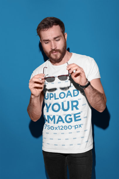 Transparent Round Neck Tee Mockup of a Man Holding Sunglasses in a Photo Studio 18698