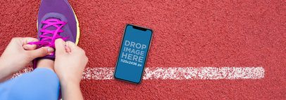 iPhone X Mockup Lying on a Running Track Next to a Person a17541
