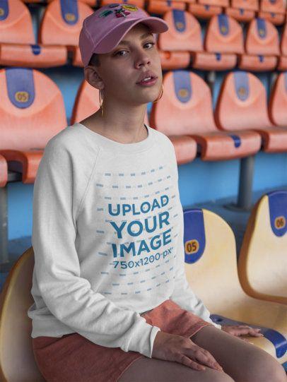 Girl Wearing a Crewneck Sweatshirt Mockup While Sitting at an Empty Stadium a18409