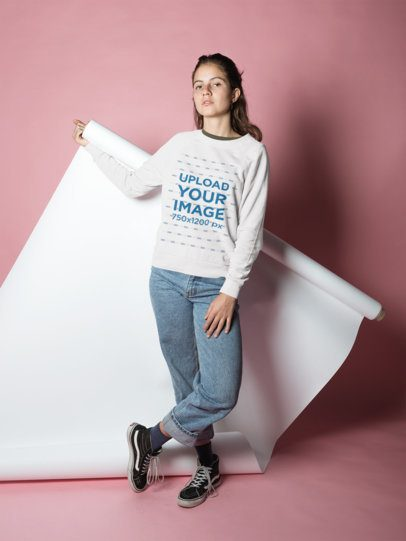 Girl Wearing a Crewneck Sweatshirt Mockup Posing in a Pink Studio a18497