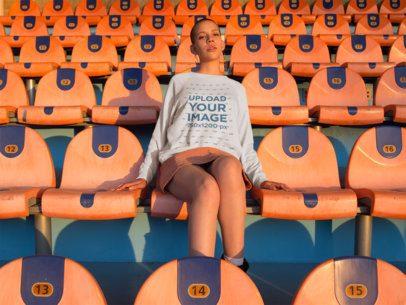 Mockup of a Shaved Head Woman Wearing a Crewneck Sweatshirt Sitting at a Stadium a18407