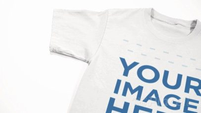 Closeup T-Shirt Video Mockup of a Round Neck Tee Lying on a White Surface a12352