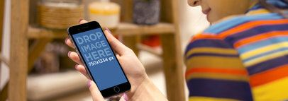 Mockup of a Woman Using an iPhone 6 in Portrait Position While Shopping Wide