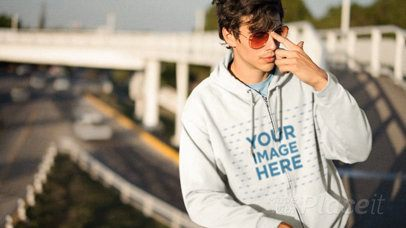 Young Man Wearing a Full Zip Hoodie Cinemagraph and Sunglasses Near the Highway a13333