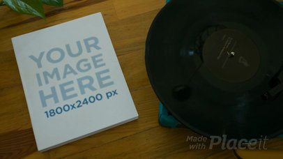 Video of a Book Lying Alongside a Turntable with a Vinyl on It Mockup a14013b