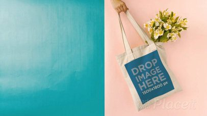 Hand Swinging a Tote Bag in Stop Motion Against Bicolored Background With Flowers a13664
