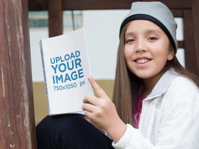 Smiling Girl Holding a Book Mockup at the Park a19108