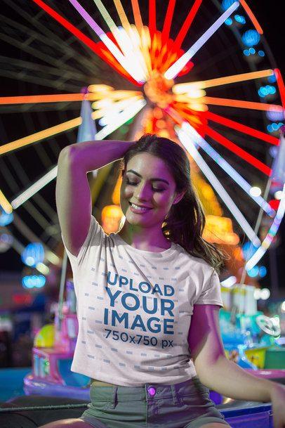 Beautiful Woman Posing Wearing a T-Shirt Mockup Near a Ferris Wheel a19452