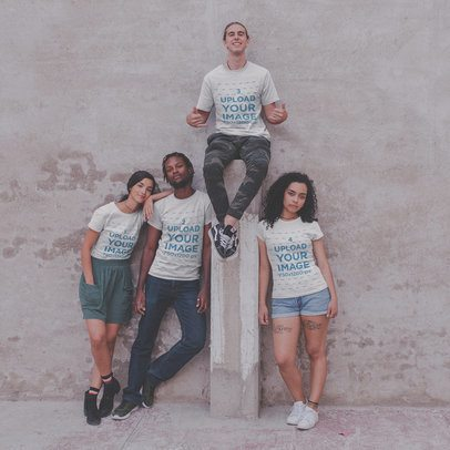 Interracial Group of Four Teens Wearing T-Shirts Mockup Against a Concrete Wall a20098