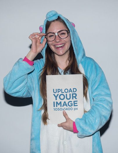 Happy Woman Holding a Book Mockup Dressed as an Unicorn a19259