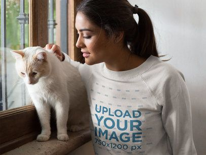 Closeup of a Beautiful Woman Wearing a Crewneck Sweatshirt Mockup Petting a White Cat Near a Window a18783
