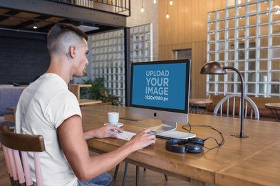 Man Working with an iMac Mockup at a Modern Place a20753