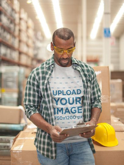 Warehouse Worker Wearing a T-Shirt Mockup While Checking the Inventory a20445