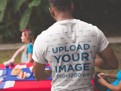 Back of a Black Man Wearing a T-Shirt Mockup at a 4th of July BBQ Party a20822