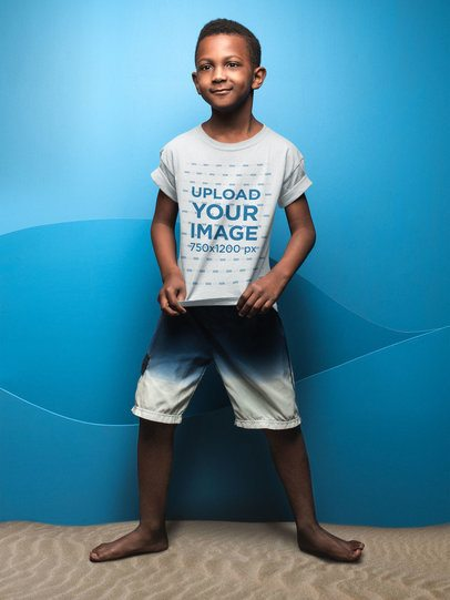 Kid Showing his T-Shirt Mockup Against a Blue Wall a19911