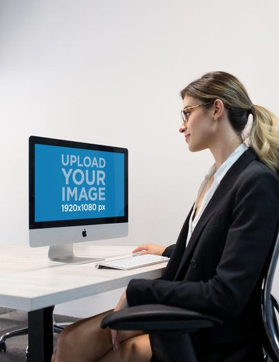 Woman Working with an iMac Mockup at the Office a20972