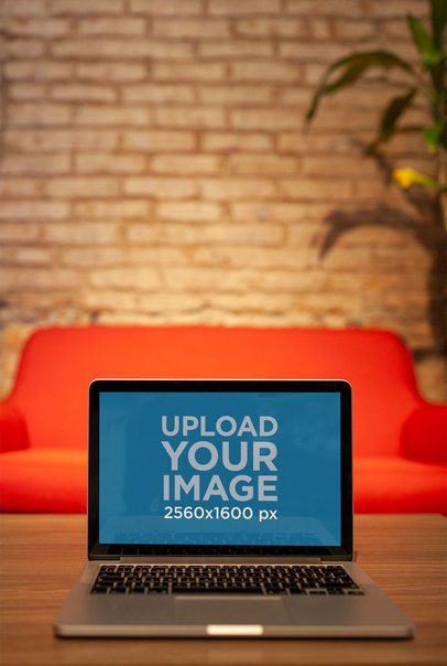 MacBook Mockup Standing on a Wooden Table Against a Red Sofa a21001