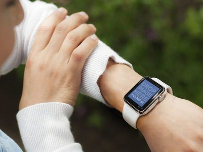 Busy Young Woman Using Her White Apple Watch Outdoors Mockup Template