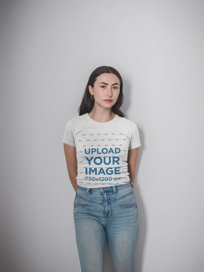 Mockup of a Girl Wearing a Round Neck Tee and Light Wash Jeans Posing Against a White Wall 19750