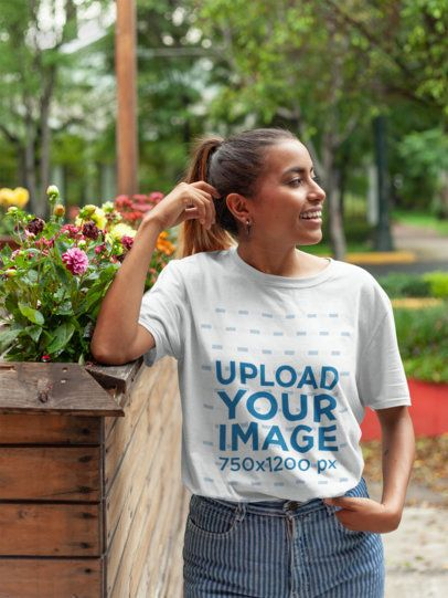 Mockup of a Smiling Girl Wearing a Tshirt Leaning Against Flowers 22796