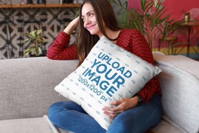 Mockup of a Happy Girl Holding a Pillow Sitting on a Sofa 23607