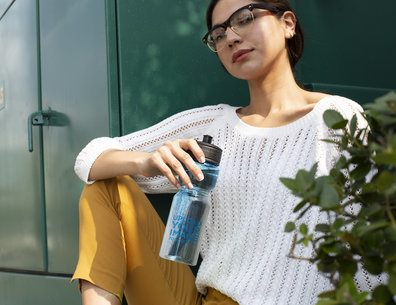 Water Bottle Mockup Featuring a Girl Sitting by a Green Electricity Box 24422