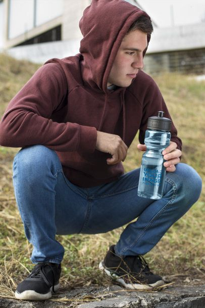 Water Bottle Mockup Featuring a Man Crouching in the Field 24440a