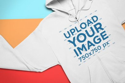 Mockup of a Full Zip Hoodie Lying Over Colored Pasteboards 24540