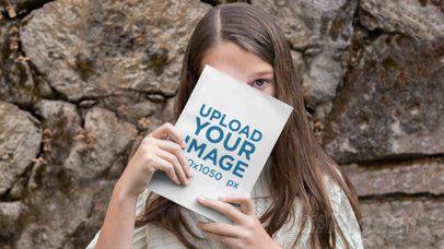 Parallax Video Mockup of a Girl Hiding Behind a Book 25922