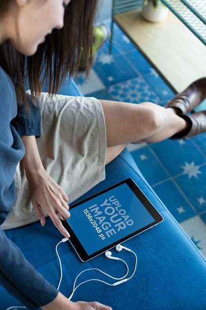 Mockup of a Girl Looking at Her Ipad 6 Screen on a Blue Couch 24797