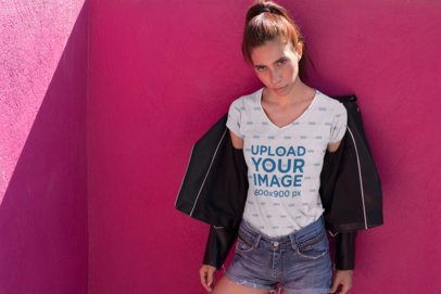 V-Neck T-Shirt Mockup of an Audacious Woman with an Open Jacket Leaning over a Wall 24979