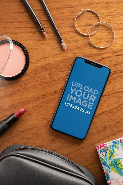 Mockup of an iPhone XS Lying on a Table with Makeup Tools 25487