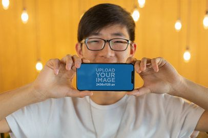 Mockup of a Happy Man with Glasses Showing His iPhone XS 25539