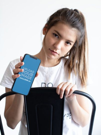iPhone XS Max Mockup Featuring a Girl Sitting Backwards on a Chair 25828